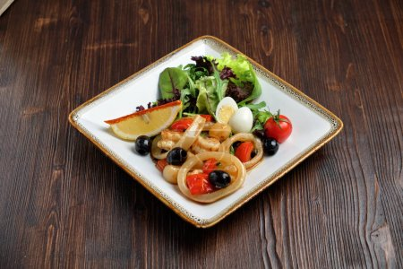 Photo pour Seafood with greens and vegetables on a white plate on a dark wooden background. catering menu - image libre de droit