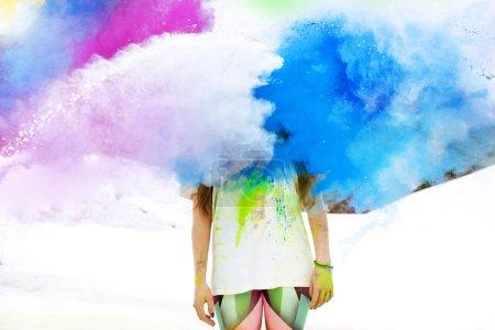 Photo pour Femme se tient dans des éclaboussures colorées ou des nuages de poudre holi - image libre de droit