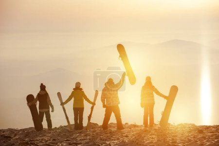 Photo for Group of skiers and snowboarders at sunset. Ski resort concept - Royalty Free Image