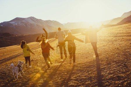 Photo pour Grand groupe d'amis heureux courir et sauter au champ de coucher de soleil contre les montagnes et le soleil - image libre de droit