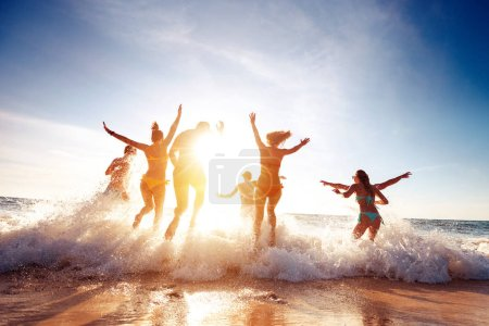 Photo for Big group of seven happy friends is having fun and runs at sunset beach to sun light and waves - Royalty Free Image