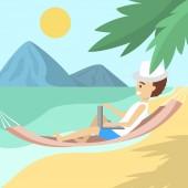 Male freelancer in the hammock on the beach