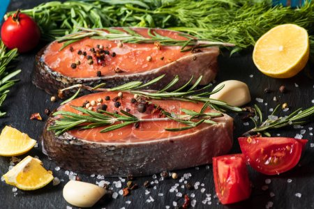 Photo for Raw fresh salmon fish before being cooking , with onion, rosemary, salt, tomato, spices, on ice, on black board - Royalty Free Image