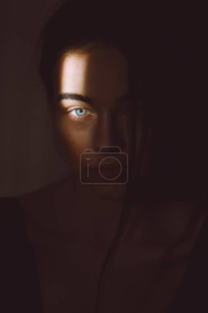 Portrait of beautiful woman in darkness with soft light on her face