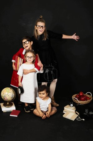 three beautiful schoolgirls from different clases and pre school boy on a black background