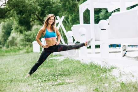 Sportive young woman in sportswear doing exercises outdoors