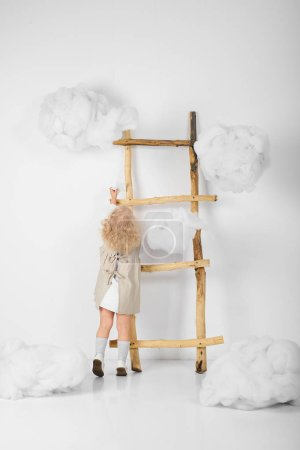 Photo for Cute little girl near the ladder in the midst of clouds on a white background - Royalty Free Image