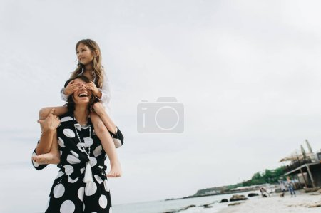 Photo for Mother and daughter holding hands and walking on beach. Mom and dauther happy family lifestyle concept - Royalty Free Image