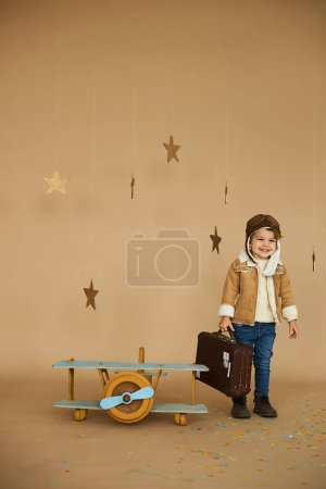 Photo for Concept of dreams and travels. pilot aviator child with a toy airplane and suitcase plays in a beige background - Royalty Free Image