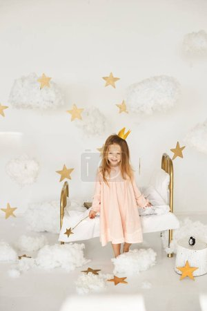 Photo for Little princess with a magic wand on  bed in a cloud - Royalty Free Image