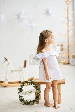 Photo for A beautiful little girl sitting on a wooden stool in a beautiful dress in the white room - Royalty Free Image