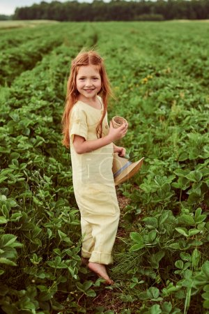 Photo for A little beautiful caucasian girl in the green field harvests and eating strawberries having fun - Royalty Free Image