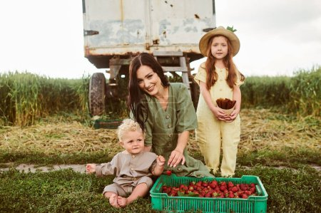 Photo for Beautiful young caucasian mother with her children in a linen dress with a basket of strawberries gathers a new crop and has fun with the children near the trailer - Royalty Free Image