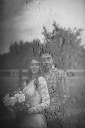 Photo pour Beau jeune couple marié et mariée marchant près de la clôture en bois - image libre de droit