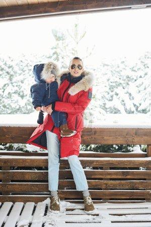Photo pour Un portret de belle jeune mère vêtue d'une veste rouge avec un enfant dans ses bras en hiver près de la maison avec un arbre de Noël recouvert de neige en arrière-plan - image libre de droit