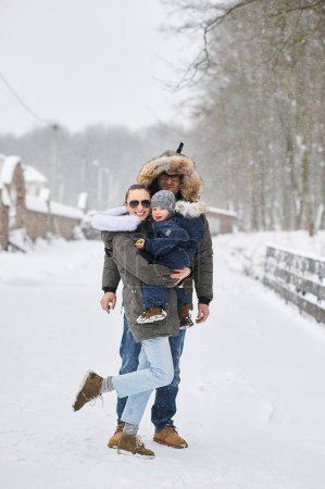 Photo for Happy family have a fun outside near the house in winter - Royalty Free Image