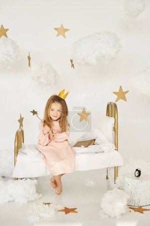 Photo for Little princess with a magic wand on a bed - Royalty Free Image