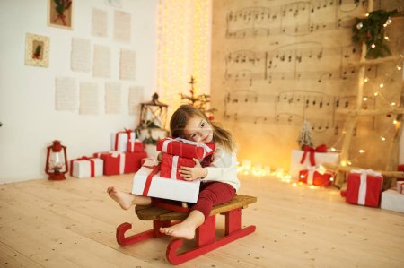 Photo for A portrait of a little girl on a red sled with a present on a blurred lights background - Royalty Free Image