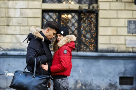 Photo for A trendy young couple walks in the city at christmastime - Royalty Free Image