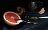 """Постер, картина, фотообои """"Вырезанный розовый грейпфрут с ножом и ложкой на темной поверхности"""""""