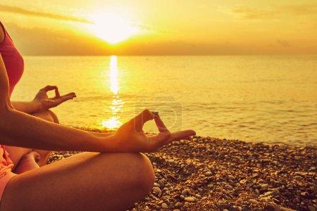 Photo pour Concept de yoga. femme main pratiquant lotus pose sur la plage - image libre de droit