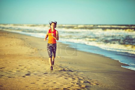 Photo for Running woman. Female runner jogging during outdoor workout on beach listening - Royalty Free Image