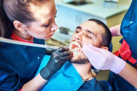 Photo pour Dentiste au travail sur un patient à la clinique - image libre de droit
