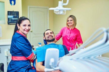 Photo pour Patient souriant et satisfait dans un cabinet dentaire - image libre de droit