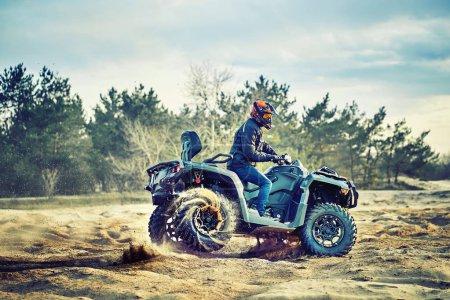 Adolescente cabalgando ATV en dunas de arena haciendo un giro en la arena