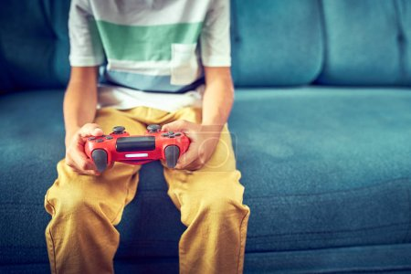 Photo for Hands using video game controller, on the couch at home - Royalty Free Image