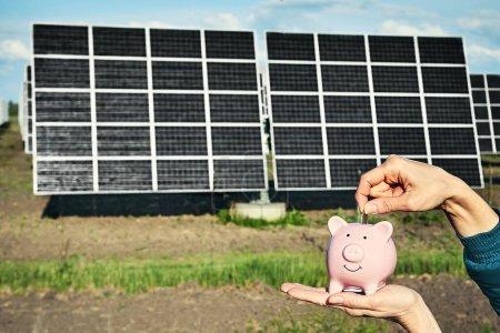 Foto de Billete de mano con paneles fotovoltaicos de energía solar en segundo plano , - Imagen libre de derechos