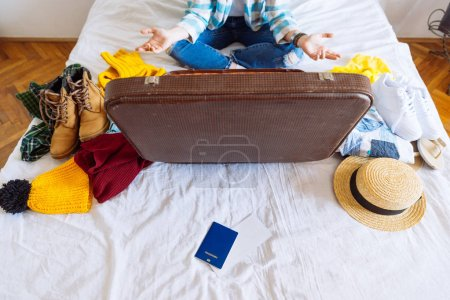 Photo for Suitcase with winter and summer clothes on bed. preparing for trip. suitcase with garment. travel concept - Royalty Free Image