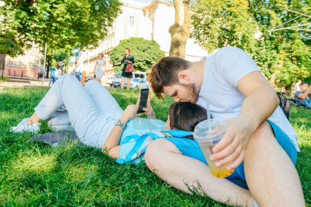 Photo for Couple resting on grass in city park. drinking smoothie surfing phone - Royalty Free Image