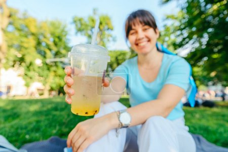 Photo for Woman holding cool drink in city park. blurred background. wide angel - Royalty Free Image
