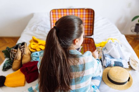 Photo for Woman sit on bed with suitcase and clothes around. travel concept. decide warm or cold country to go. - Royalty Free Image