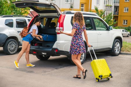 Photo for Two woman packing luggage in car trunk. road trip - Royalty Free Image