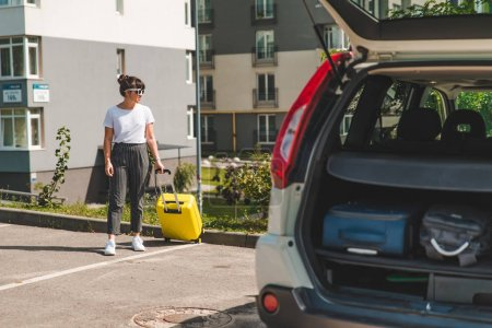Photo pour Femme pull valise à roulettes pour coffre de voiture. voyage sur la route. concept de voyage de voiture. - image libre de droit