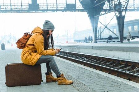 Photo pour Femme attente pour le train à la gare. concept de voyage. surfer sur internet sur le téléphone pour tuer le temps - image libre de droit