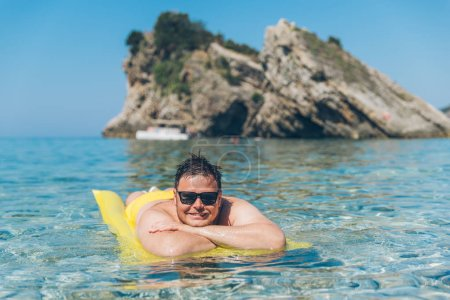 Photo for Young man at yellow inflatable mattress in clear transparent water. summer vacation concept - Royalty Free Image