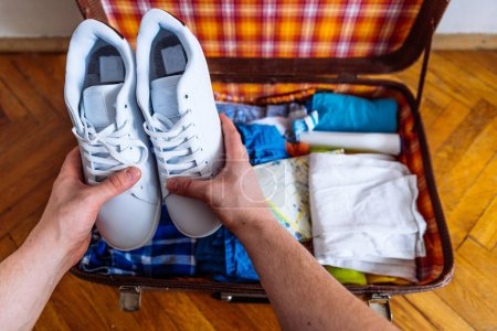 Photo for Hands put sneakers to valise. packing for trip. travel concept - Royalty Free Image