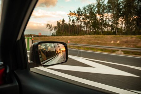Photo for Car on highway. sunset in car mirror reflection. road trip - Royalty Free Image