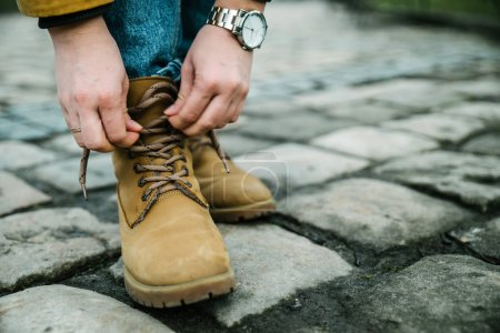 Photo for Girl laces up shoes in autumn day - Royalty Free Image