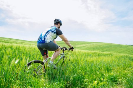 Photo for Young strong man riding bicycle by green field - Royalty Free Image