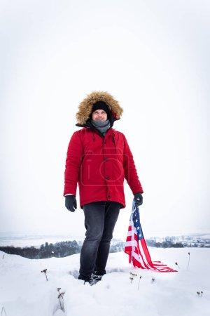 Photo pour Homme au manteau d'hiver rouge tenant le drapeau usa à l'extérieur par temps neigeux. mode de vie patriotique - image libre de droit