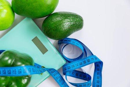 Photo pour Concept d'une alimentation saine. vue aérienne de fruits et légumes sur le poids sur fond blanc. espace copie - image libre de droit