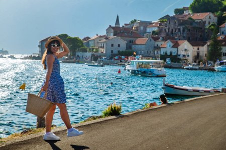 Photo for Young pretty stylish woman walking by city quay. sea and mountains on background. summer travel concept - Royalty Free Image