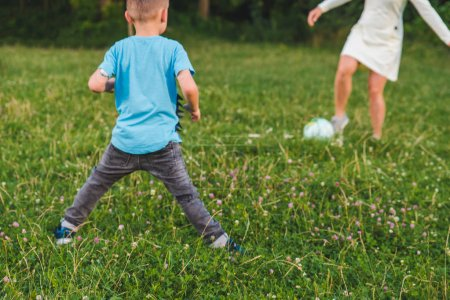 Photo for Mother play with son in ball at green field. outdoors summer time - Royalty Free Image