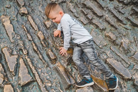 Photo for Little kid climbing by wall. playing around - Royalty Free Image