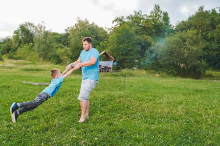 Photo for Man spinning boy at green field. playing around. fun time - Royalty Free Image