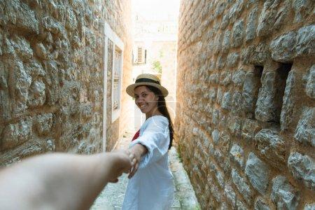 Photo pour Suivez-moi. femme tenant la main de l'homme dans la rue étroite en pierre de Budva. vacances d'été - image libre de droit